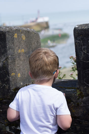 Boys Casual Clothing Childhood Day Focus On Foreground Leisure Activity Looe Nature One Person Outdoors People Real People Rear View Rock - Object Sea Sky Standing Water