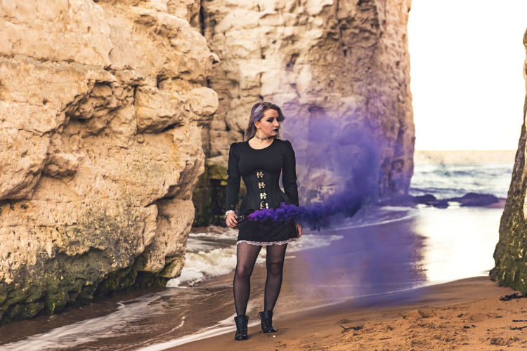 Portrait of young woman standing on rock against sea