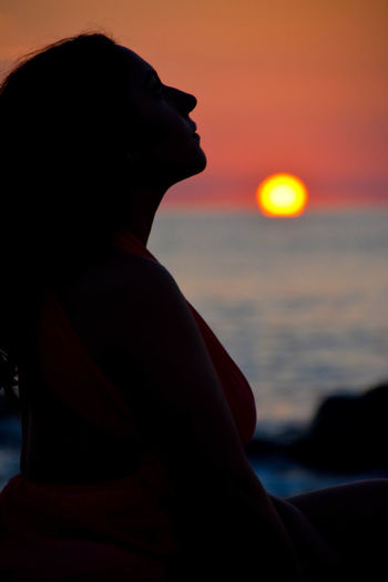 Relaxing with a sunrise view Adult Beach Beauty In Nature Land Lifestyles Nature One Person Orange Color Profile View Scenics - Nature Sea Side View Silhouette Sky Sun Sunrise Sunset Water Women