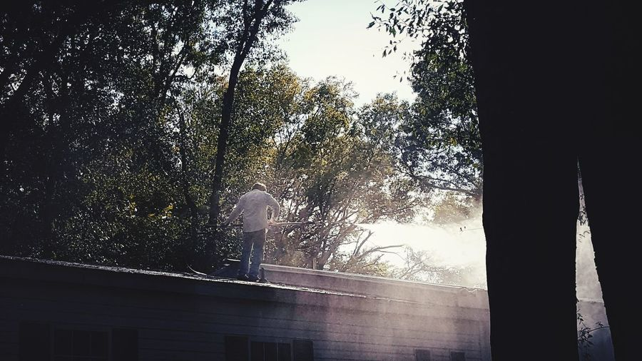 man working on roof. It is my husband, cleaning off all the acorns and tree litter. Man Louisiana Mist Trees Man Working Man On Rooftop Full Daylight Water Spraying Tree Window Silhouette Sky Architecture Water Drop