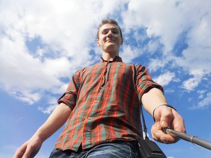 Low angle portrait of man standing against sky