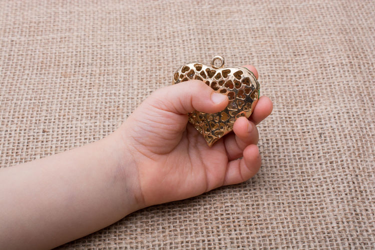 Cropped Hand Holding Heart Shape Toy On Burlap