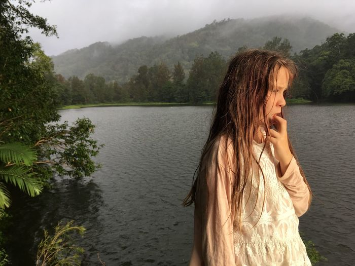 Girl standing by lake against sky