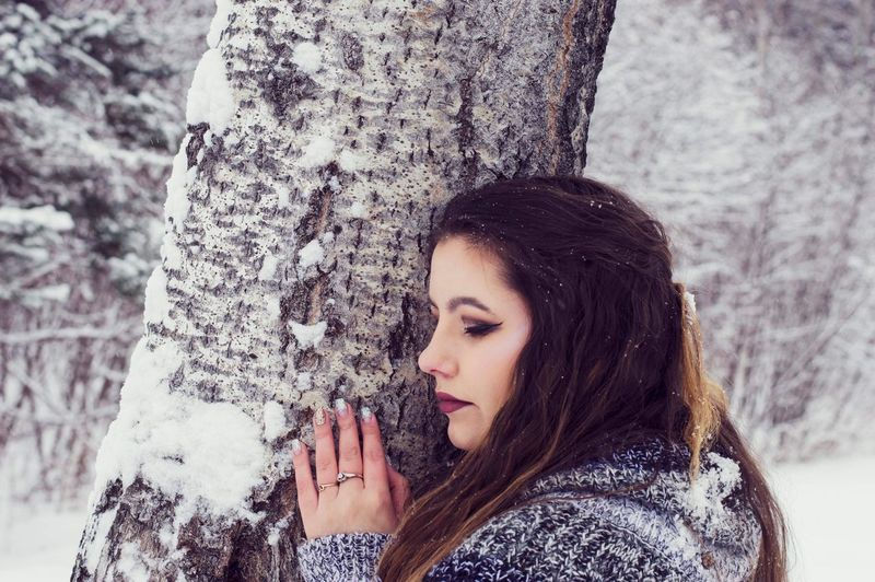 Woman against tree trunk during winter