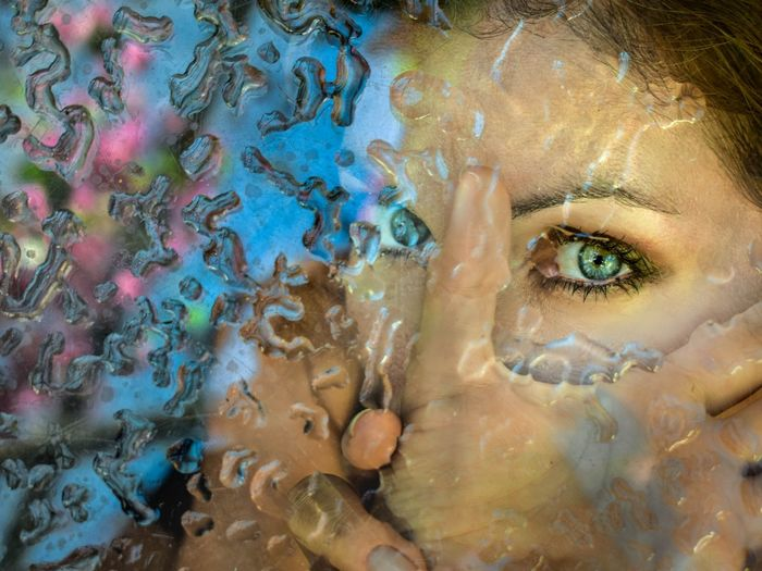 Close-up portrait of woman seen through wet window