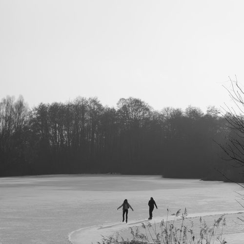 Wintertime Beauty In Nature Clear Sky Cold Temperature Copy Space Day Field Full Length Ice Skating Landscape Leisure Activity Lifestyles Men Nature Outdoors Real People Scenics Silhouette Snow Sport Togetherness Tree Two People Winter Winter Sport Black And White Friday Be. Ready.