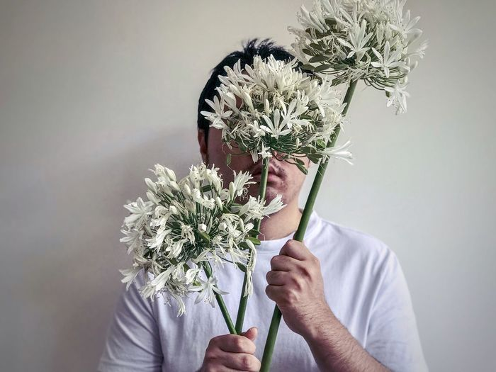 Man holding 3 stalks of white, african lilies flowers against white background.