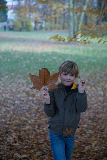 Little blond boy playing with autumn leaves in park Alone Autumn Autumn Blond Casual Clothing Childhood Memories Color Day Front View Germany Hapiness Happy Child  Jumping Leaf Leaves One Person Outdoor Outdoors Park Playful Real People Running Smiling Tree Young Adult