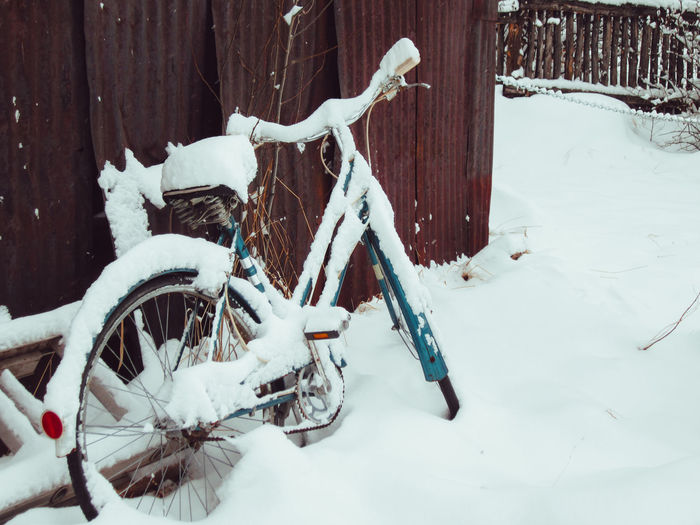 Snow covered bicycle on field