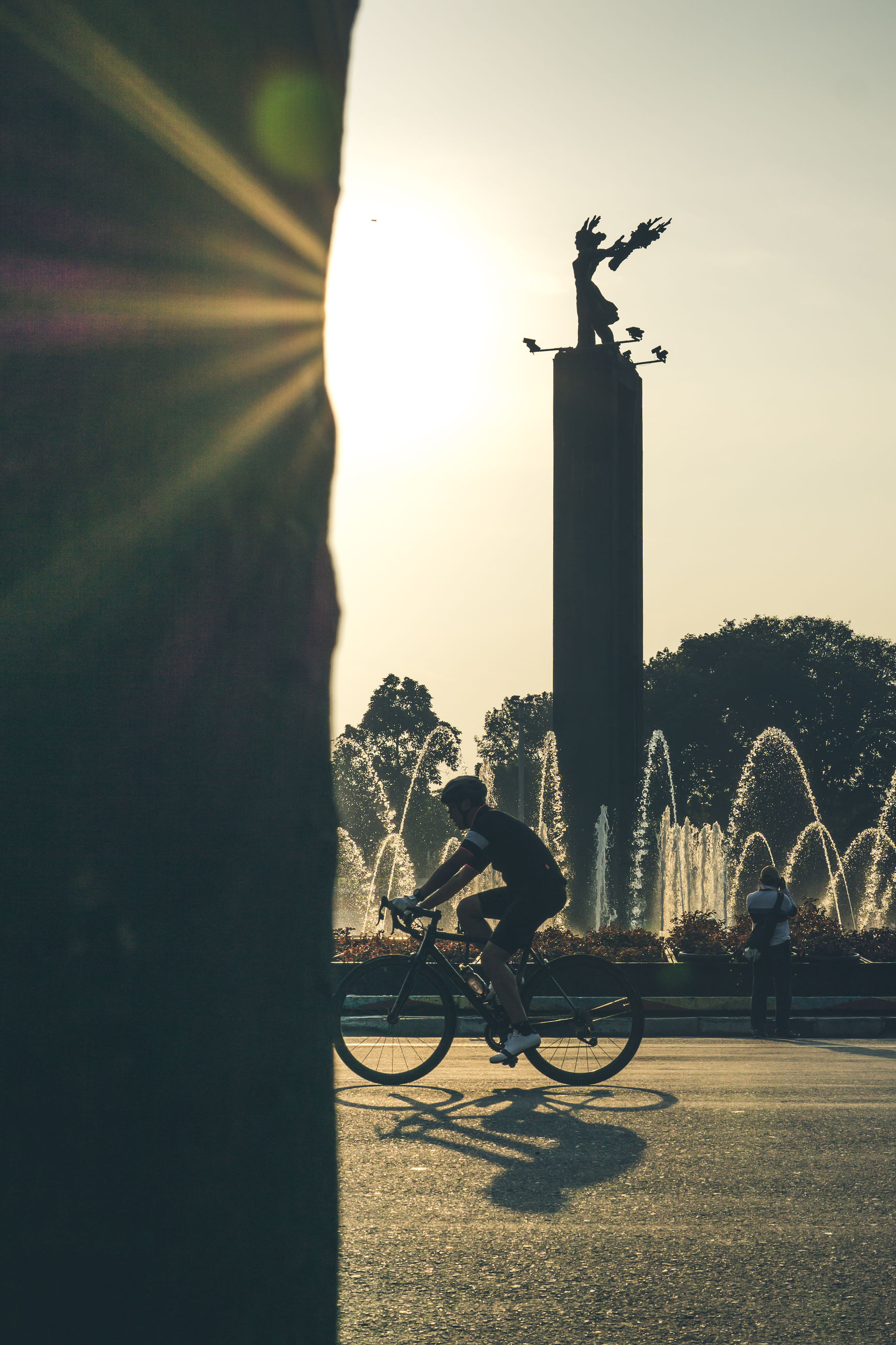 bicycle, nature, sculpture, statue, sky, architecture, art and craft, sunlight, transportation, plant, representation, human representation, mode of transportation, built structure, outdoors, building exterior, land vehicle, no people, day, city, lens flare, architectural column