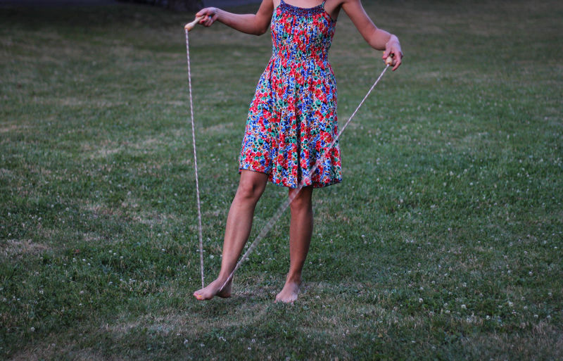 Low section of woman holding jumping rope