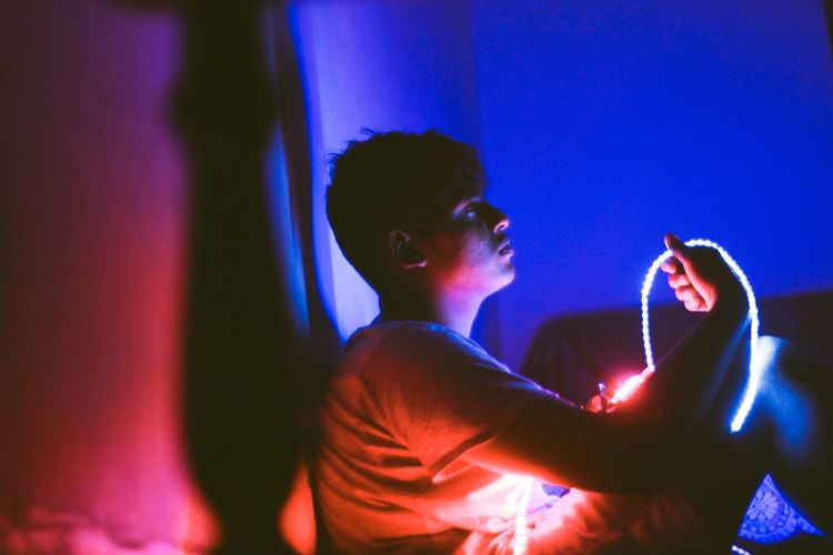 Man sitting in illuminated room