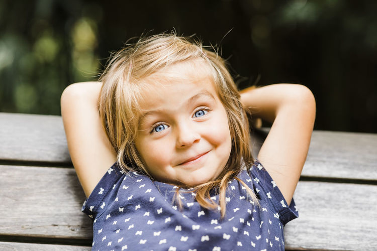 Portrait of cute smiling girl sitting on bench