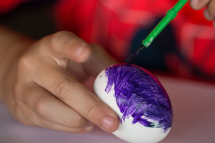 Midsection Of Child Coloring Easter Egg