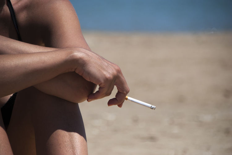 Midsection of woman smoking cigarette at beach