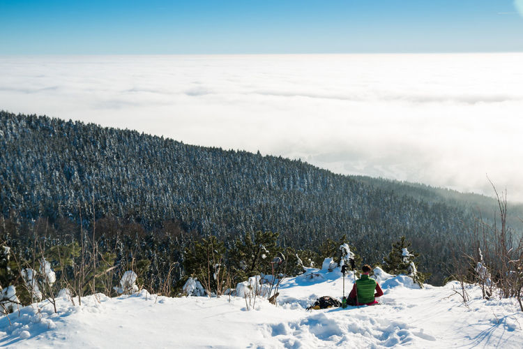 Scenic View Of Man Sitting On Snow Covered Landscape Against Sky