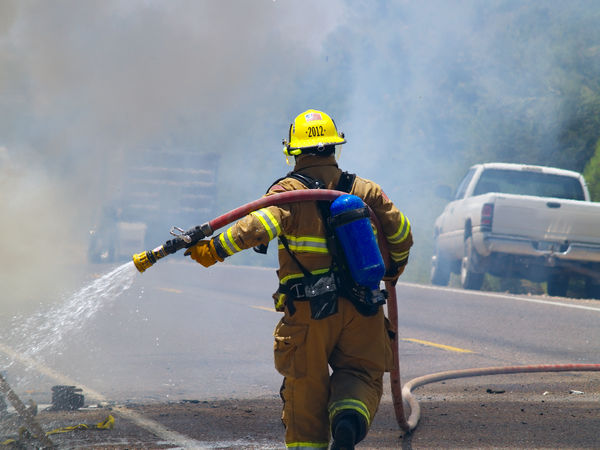 A firefighter extinguishing a vehicle fire along an Arizona road. Firefighter's face is not visible, no model release is necessary. Arizona Accidents And Disasters Courage Danger Day Emergency Equipment Fire Engine Fire Hose Firefighter Headwear Helmet Men Motion Occupation One Person Outdoors People Protective Workwear Real People RISK Spraying Water Working