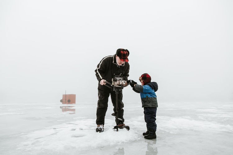 Senior Man With Grandson Using Machinery On Frozen Lake