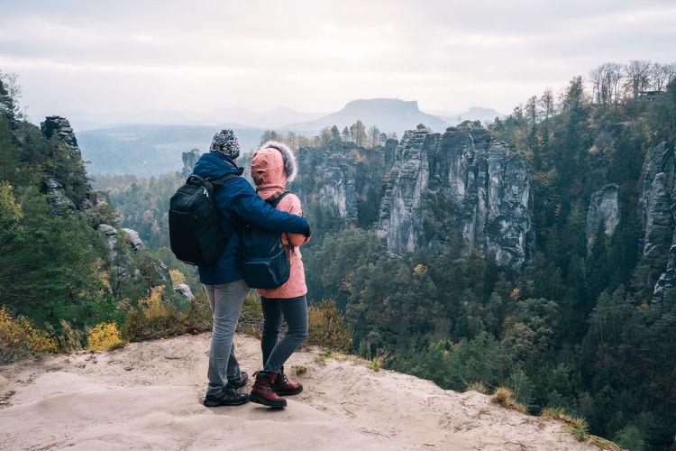 Full length of couple standing on mountain against sky
