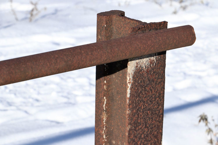 Close-up of rusty metal fence during winter