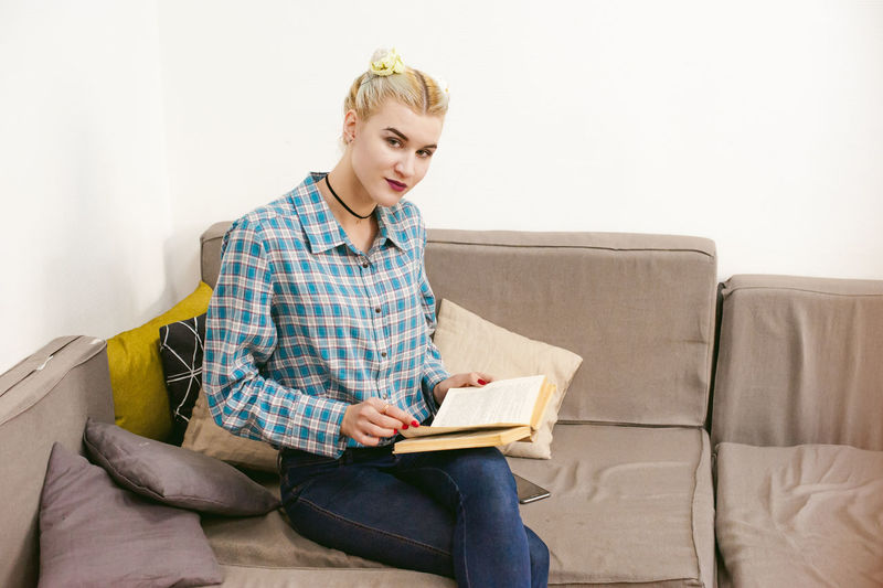 Portrait Of Young Woman Reading Book While Sitting On Sofa At Home
