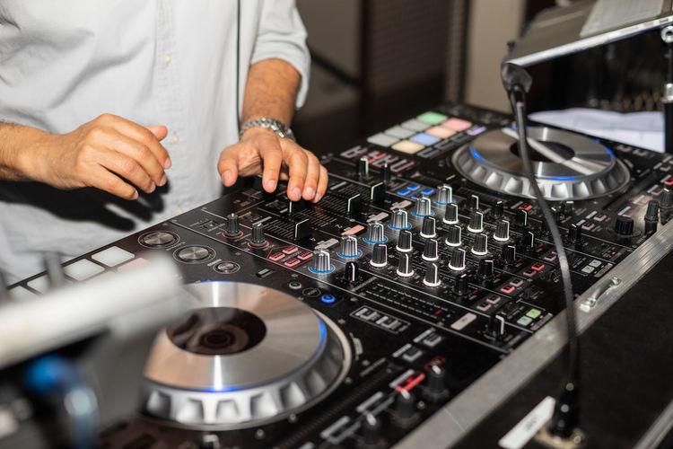 Hands of dj tweak various track controls on dj sound mixer