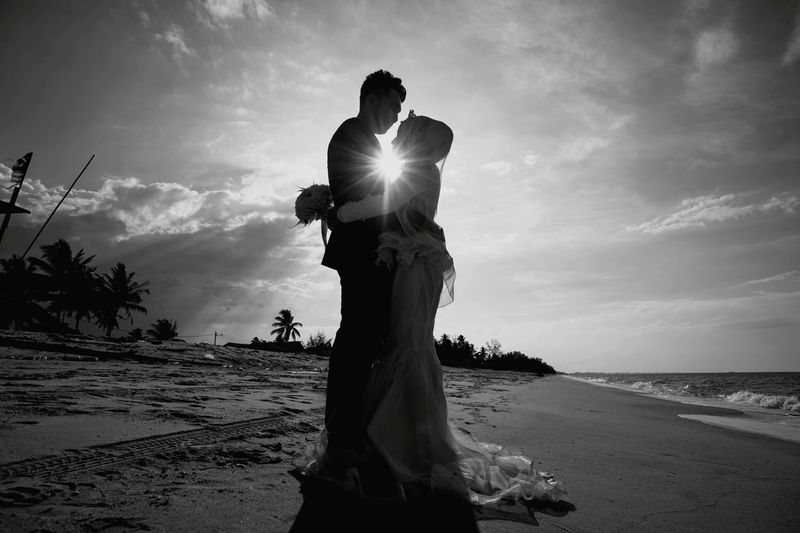 Side View Of Couple Embracing While Standing On Shore At Beach