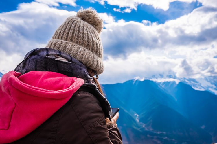 Young woman using mobile phone while standing against sky during winter