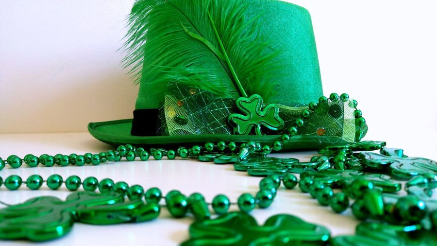 Green hat with feather and beads necklace for saint patrick day celebration.