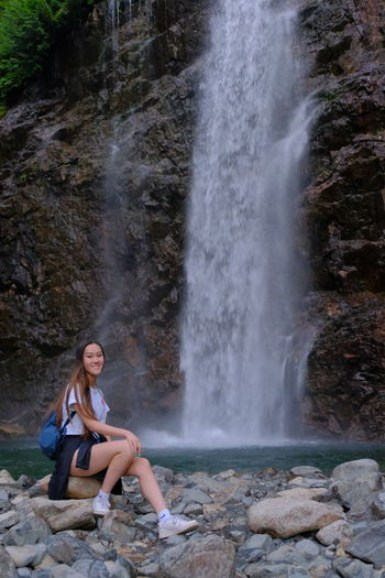 Full length of young woman sitting on rock by waterfall