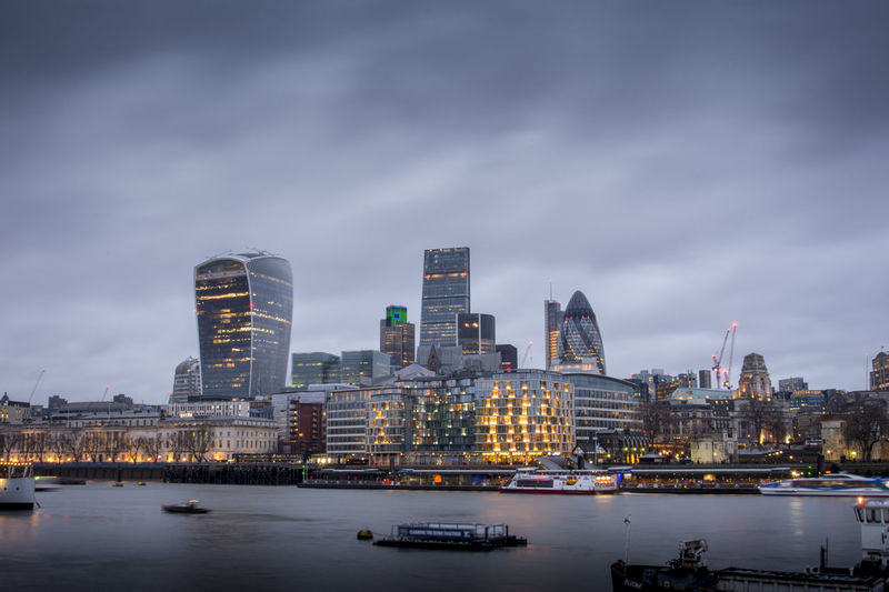 High angle view of thames river against modern buildings at dusk