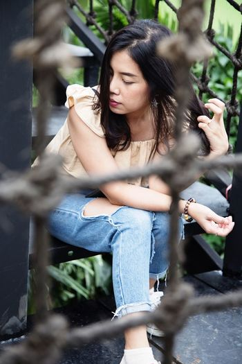 Young woman looking away while sitting outdoors