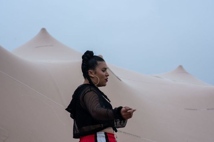 Contemplate One Person Real People Lifestyles Leisure Activity Arid Climate Climate Outdoors Day Land Nature Beauty In Nature Scenics - Nature Standing Casual Clothing Environment Sky Young Adult Young Women Side View Tent Bedouin