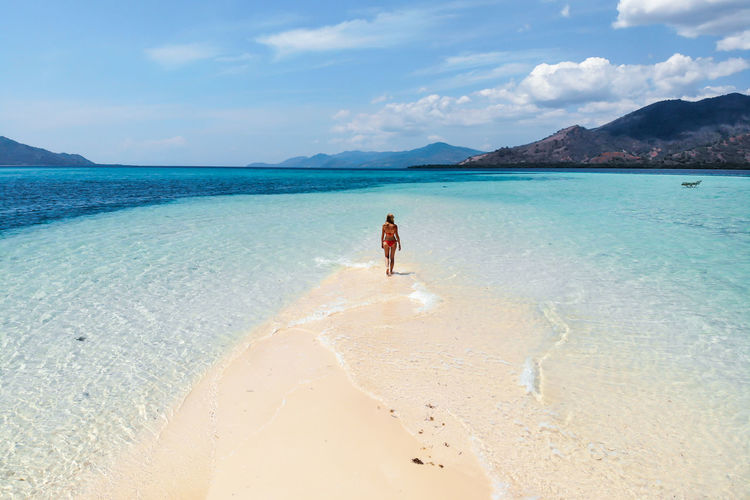 Rear view of woman walking on sand bar at beach against sky