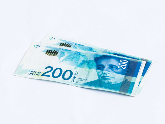 Two new banknotes worth 200 Israeli new shekels on a white background Wealth Banknotes Business Currency Economy Foreign Rich Bank Banknote Cash Close-up Commerce Credit Debt Economic Finance Investment Israel Money Paper Pay Profit Saving Shekel White Background