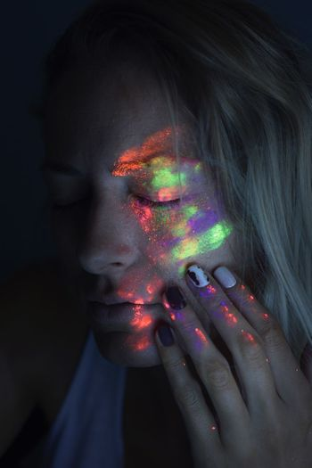 Woman With Multi Colored Painted Face Against Black Background
