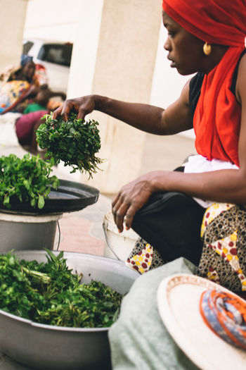 Young woman wearing headscarf holding vegetables while crouching outdoors