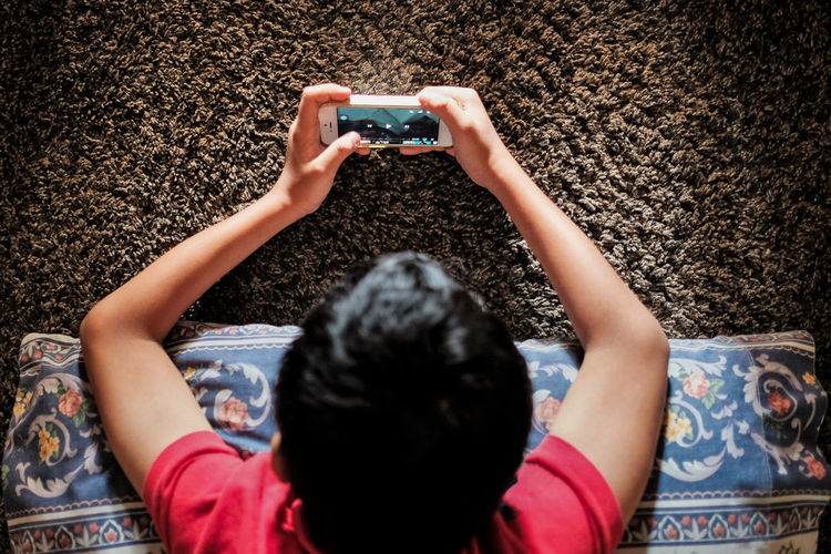 High angle view of boy playing video game in smart phone at home