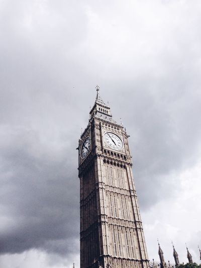 Low angle view of clock tower against cloudy sky