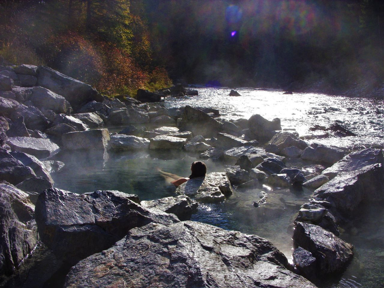 Rear View Of Woman Sitting In Hot Spring At Whiteswan Lake Provincial Park
