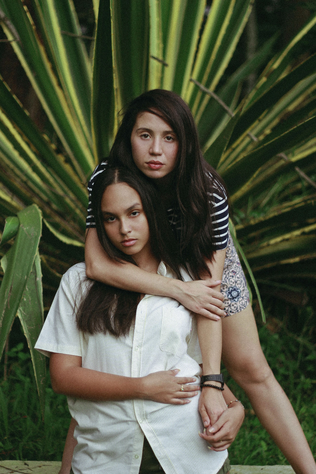 Portrait Of Two Sisters Standing Against Plants