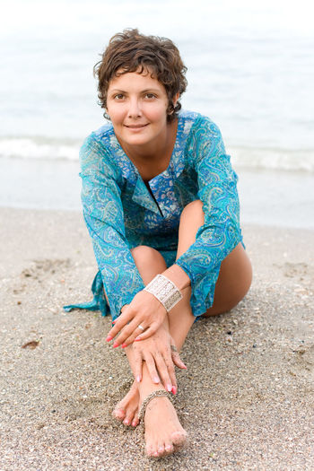Portrait of smiling woman sitting on beach