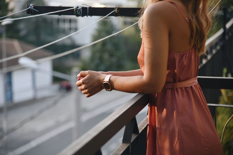Midsection of woman standing at railing