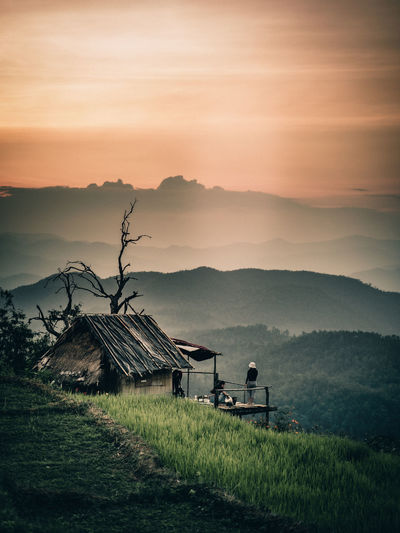 Friends by hut against mountains during sunset