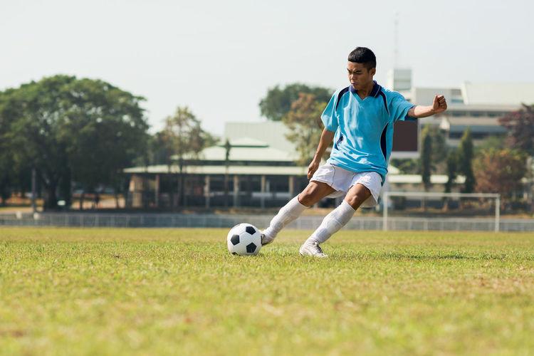 Full length of man playing soccer ball on grass
