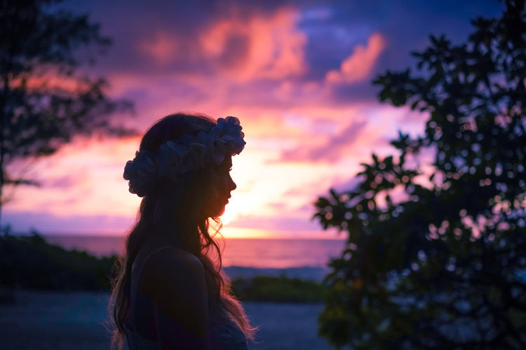 Side view of woman wearing tiara standing against sky at sunset
