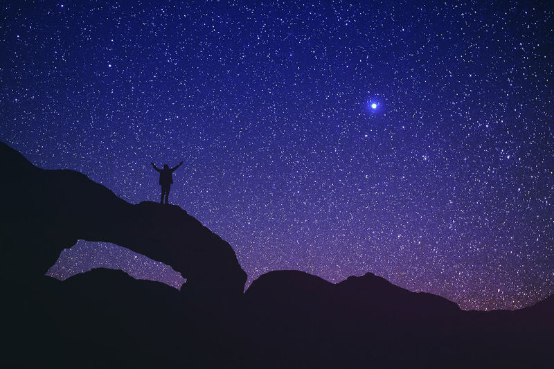 Low angle view of silhouette person standing on rock formation against star field in sky at night