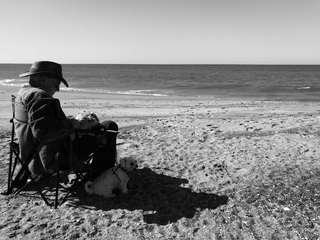 Afternoon at the beach. Sitting One Person Adult Full Length Outdoors One Man Only People Day Sky NoEditNoFilter EyeEmNewHere Horizon Over Water Vacations Tranquility Clear Sky Nature Animallovers Togetherness Shades Shadows & Lights Monochrome _ Collection EyeEmNewHere