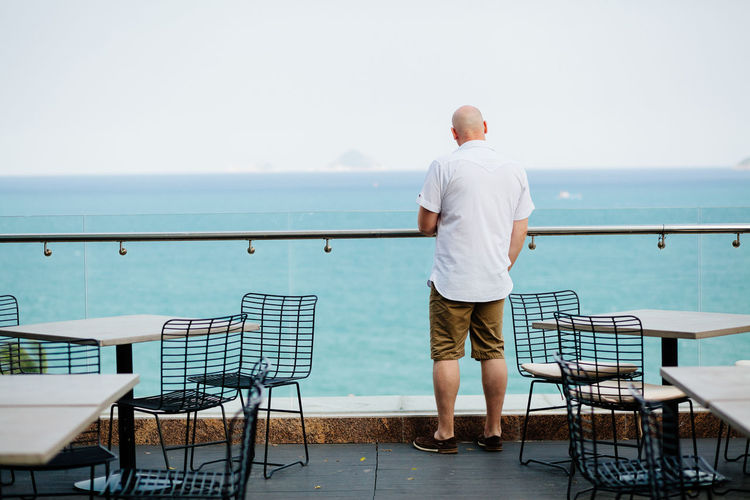 Rear view of man standing on terrace restaurant by sea