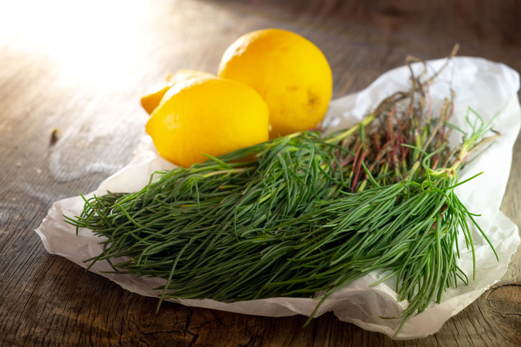 Agretti on wooden table with lemons Food And Drink Salad Agretti Close-up Cutting Board Food Food And Drink Foodphotography Freshness Fruit Green Color Healthy Eating Herb Indoors  Leaf Lemons No People Plant Part Raw Food Rosemary Still Life Table Vegetable Vegetables Wellbeing Wood - Material